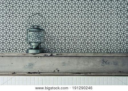 Vintage kerosene oil lantern lamp standing on wooden shelf with texture wall background. (Vintage filter effect)