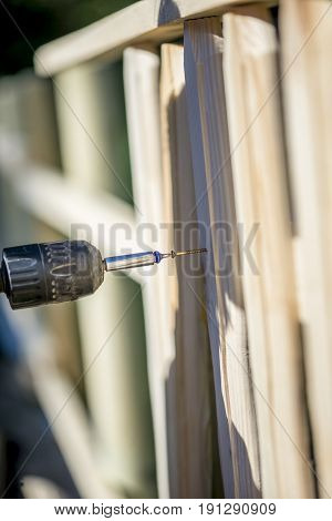 Person building a wooden fence with a drill and screw using a hand held power drill.
