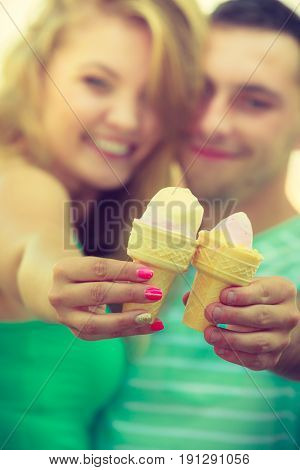 Relationship goals summer love concept. Man and woman being on date eating ice cream on beach
