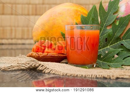 Fresh papaya juice in the glass with papaya fruits papaya leaf and papaya slices on sackcloth.Background of a straw mat and a clay pot.Raw food diet. Selective focus.