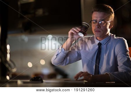 Tired businessman working late doing overtime in office at night drinking coffee to stay awake.