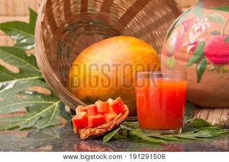 Fresh papaya juice in the glass with papaya fruits papaya leaf and papaya slices.Background straw mat and a clay pot.Raw food diet. Selective focus.