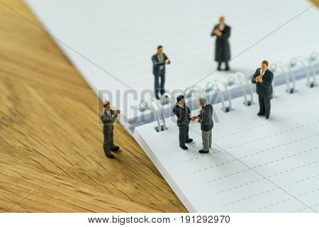 Miniature people with small figure businessmen handshaking and others clapping on notebook and pencil as business agreement concept.