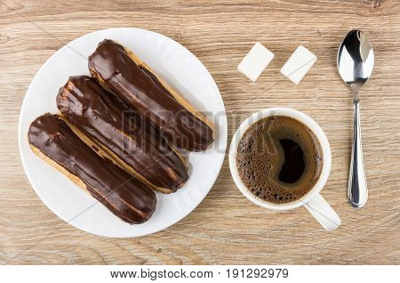 Eclairs With Chocolate In Plate, Coffee In Cup, Lumpy Sugar