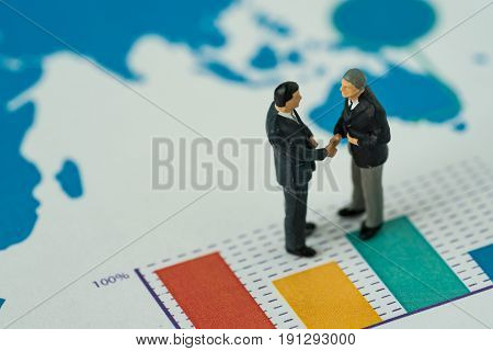 Miniature people with small figure businessmen handshaking on printed analysis bar chart as business agreement for success concept.