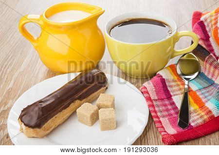 Eclair With Chocolate, Lumpy Sugar In Plate, Black Coffee, Milk