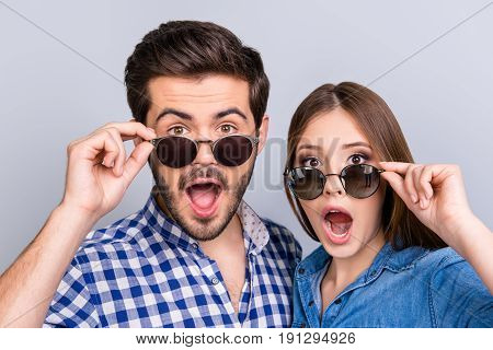 Really?! Two young shocked lovers are amazed with wide open eyes mouthes fixing in a casual wear on light background