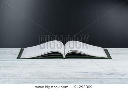 Open book on wooden deck table and black board background. Back to School. Education concept with copy space for your ad text
