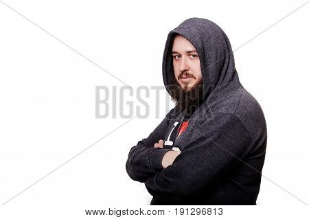 A serious bearded man, dressed in a hood with arms crossed over his chest, with a hood on his head.