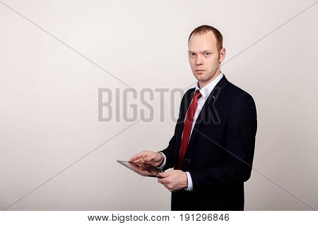 elegant young businessman keeps the tablet in hands, watching straight.