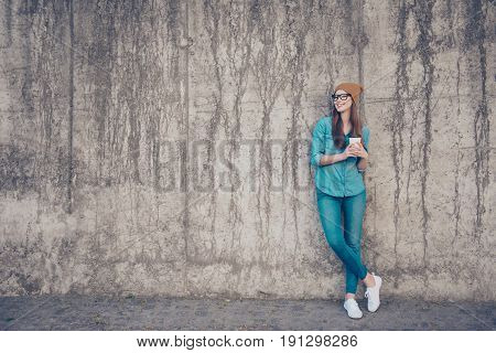 Full Size Of Cheerful Young Lady, Standing Near Concrete Wall Outside, Smiling, With Crossed Legs An