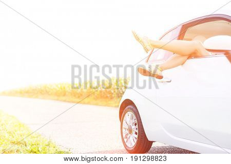 Low section of woman relaxing in car on country road against clear sky