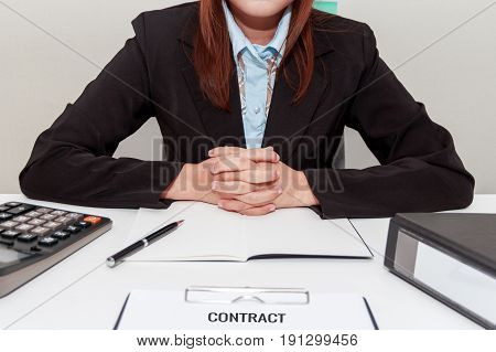 Businesswoman holding her own hands while sitting at desk - signing contract concept