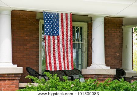 old brick home with white pillars and American flag hanging on front porch