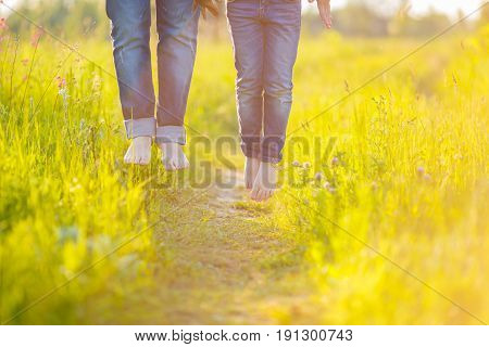 A young married couple jumps high on a trail laid in a rush of juicy grass on a meadow. Legs of a man and women hang in the air