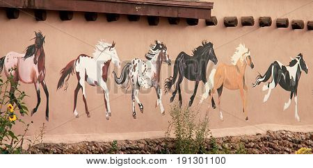 Taos, New Mexico - October 1, 2011. Mural depicting wild painted horses on walls of old town. Taos is world famous for arts and culture.