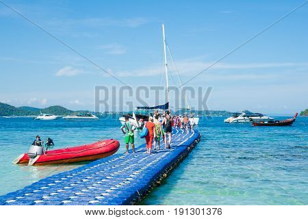 Tourists return from the Banana beach of Coral (Ko He) island and go to the motor boat. Rawai, Phuket, Thailand