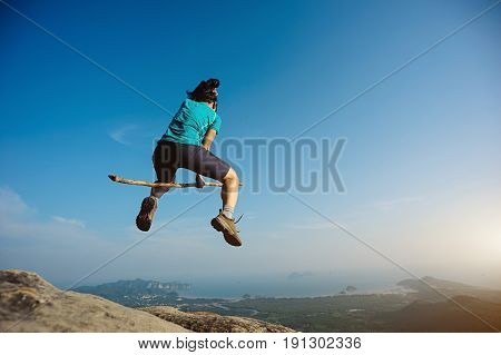 cheering woman jumping on rocky mountain top