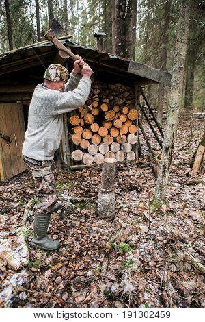 Hunter chopping wood near a hunting lodge