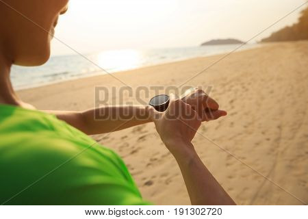 young woman runner set the sports watch before run on beach