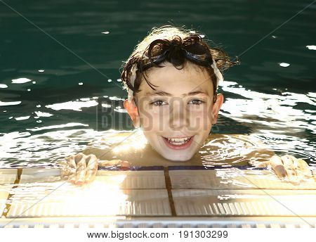 teen happy boy in the swimming pool close up smiling portrait