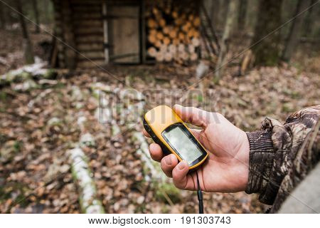 Man the hunter with a GPS navigator in the forest. hunting lodge, a backpack, a gun. Technology, Gadget.