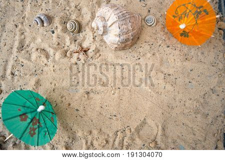 Umbrella for cocktails on a sandy summer background