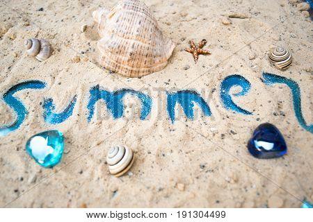 Inscription summer on a sunny sandy beach