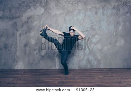Young Cute Dancer Is Making His Move, Touches Head And Holds The Foot On The Grey Background