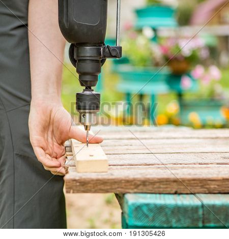 Man screws board with drill in park