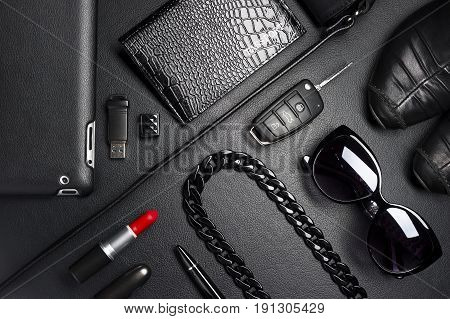 Woman accessories in business style, red lipstick, gadgets, shoes, jewelry, car key, bag, eyewear and other luxury businesswoman attributes on leather black background, fashion industry, top view