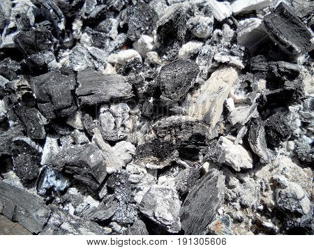 Photo of fire ashes,dark grey black coal,background texture. Wood burning in ashes. Coal flame fires,cooking barbecue.Ashes mineral cube stone,bbq grill flaming hot charcoal briquettes,fracture coals.