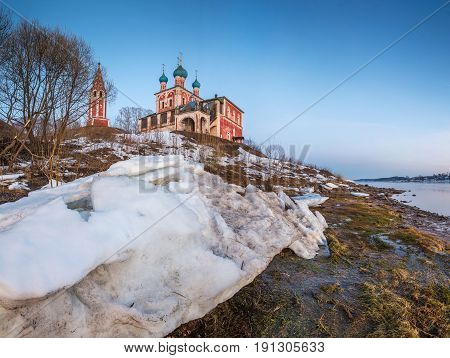 On the high bank of the Volga River there is a red church. In the foreground is a large melting snowbank. Spring ruralscape. The city of Tutaev (Romanov). Yaroslavl region.