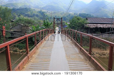 wooden hanging bridge from village to the traditional market. Northern Vietnam