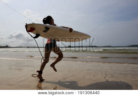 Young woman surfer wit surfboard ready to surf