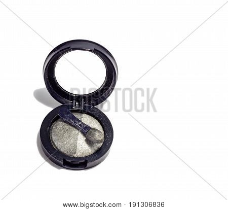 Eye shadow on white background in a black round box with a brush