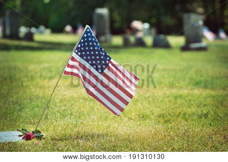 American veteran flag and a rose in the cemetery