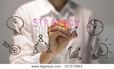 Woman writing Strategy on transparent screen. Businesswoman write on board. Drawing on desk.