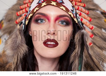 Indian woman with traditional make up and headdress looking at the camera. Redskin Indian woman on white background with a roach on her head. poster