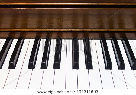 Black and white piano keys and wooden piano background