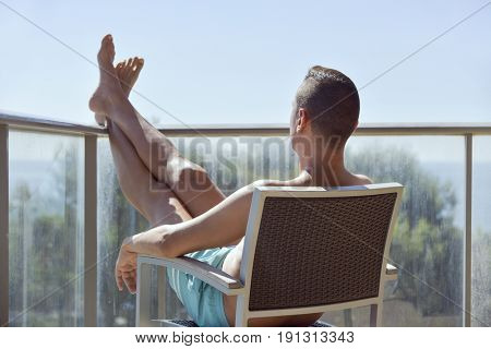 closeup of a young caucasian man in swimsuit sitting in a chair in a terrace