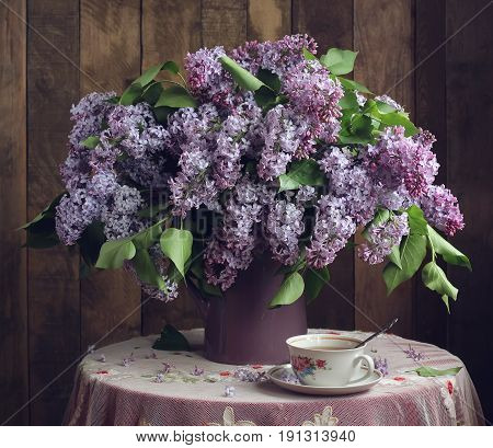 Retro still life. Bouquet of lilac and tea Cup on the table with a lace tablecloth on wooden background.