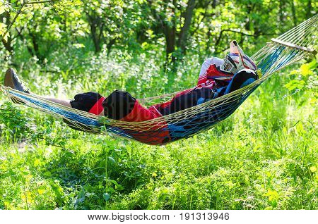 The extreme man rests in a hammock in a helmet and protects the body. An extreme kind of sport a motocross rests in the woods after the competition.