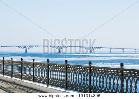 The spring ice drift on the river Volga. Road bridge in the city of Saratov. Russia. A Sunny day in March. Blue sky. Cast iron fence on the waterfront.