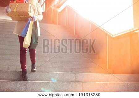 Low angle view of woman with gifts and shopping bags moving down steps
