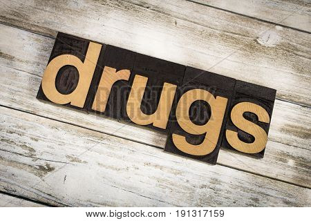 """The word """"drugs"""" written in wooden letterpress type on a white washed old wooden boards background. poster"""