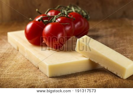 Close up of Emmental cheese with cherry tomatoes on wooden cutting board