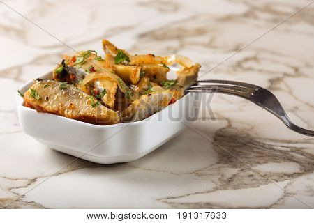 Marinated herring fish salad with onion and tomato sauce in white bowl