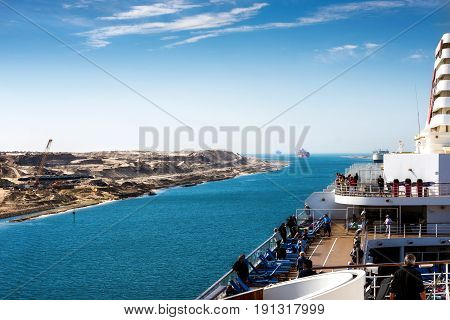 Sinai Egypt - April 2nd 2016: The Suez Canal - a ship convoy with a cruise ship passes the new eastern extension canal opend in August 2015 coming from the direction of the great Bitterlake. President al-Sisi initiated the construction to boost the  egypt