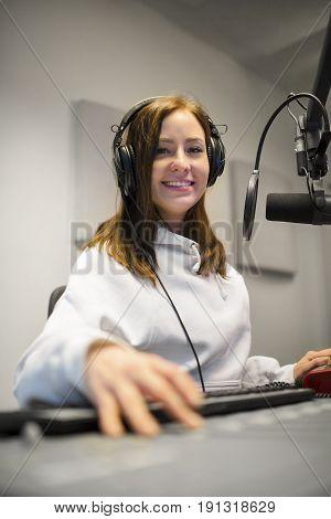 Portrait of female jockey smiling while wearing headphones in radio studio
